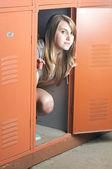 Teenage girl sits in a locker — Stock Photo