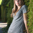 Vertical teenage girl stands near vines in the shade — Stock Photo