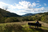 Woman hiker rests at a bench with scenic view — Stock Photo