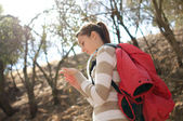 Woman checks her hand while hiking outdoors — Stock Photo
