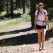 Adult womwearing shorts and t-shirt hikes through woods — Foto Stock #22250079