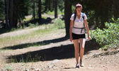 Adult woman wearing shorts and t-shirt hikes through woods — Stock Photo