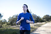 Centered close up of woman jogging outside, facing left — Stock Photo