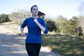 Centered close up of woman jogging outside, facing right — Stock Photo