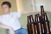 Man facing left with group of empty beer bottles, angled — Stock Photo
