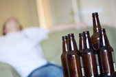 Man passed out on couch with empty beer bottles, angled — Stock Photo