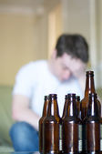 Vertical, man holding his head up with empty beer bottles — Stock Photo