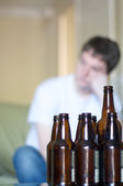 Vertical, man looking to left with empty beer bottles — Stock Photo
