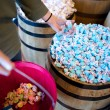 A woman has a handfull of blue salt water taffy — Stock Photo #24994669