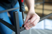 Horizontal close up of hands screwing together furniture pieces — Stock Photo