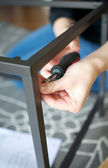 Vertical close up of hands screwing together furniture pieces — Stock Photo
