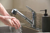 Washing hands in the kitchen sink — Stock Photo