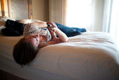 Woman reads on her phone while lying on bed — Stock Photo