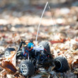 Veritcal of toy RC truck in leaves, no body — Stock Photo