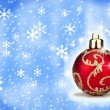 Red Christmas bauble with a snow backround — Stok fotoğraf