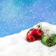 Green and red Christmas bauble in the snow — Stock Photo