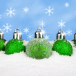 Green baubles in the snow — Stock Photo