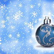 Photo: Blue Christmas bauble with a snow backround