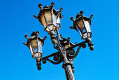 Ornate Spanish lamp post against blue sky — Stock Photo