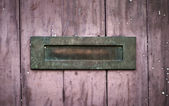 Weathered rusty letter box on red wood — Stock Photo