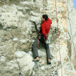 Young man climbing on a limestone wall with wide valley on the background — Stok fotoğraf