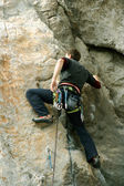 Young man climbing on a limestone wall with wide valley on the background — Stock Photo