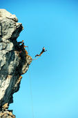 Jump off a cliff with a rope. — Stock Photo