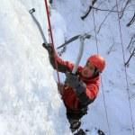 Man climbing frozen waterfall — Stock Photo #14729655