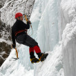Ice climber struggles up a frozen waterfall. — Stock Photo
