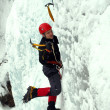 Man climbing frozen waterfall — Stock Photo