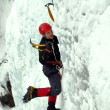 Man climbing frozen waterfall — Stock fotografie