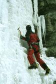 Man klättring frusna vattenfall — Stockfoto