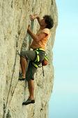 Ung man klättra på en kalksten vägg med brett dal i bakgrunden — Stockfoto