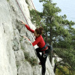 Young woman climbing vertical wall with valley view on the background - Stock Photo