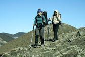 Hikers with backpacks enjoying valley view from top of a mountain — Stock Photo