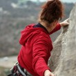 Young woman climbing on a limestone wall with wide valley — ストック写真