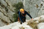 Jonge man klimmen op een muur van kalksteen met grote vallei op de achtergrond — Stockfoto