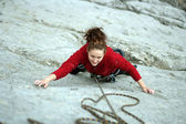 Young woman climbing on a limestone wall with wide valley — Stock Photo