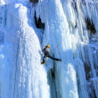 Man climbing frozen waterfall - Photo