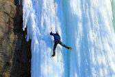 Man climbing frozen waterfall — ストック写真