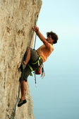 Young man climbing vertical wall with valley view on the background — Stock Photo