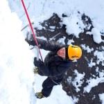 Man climbing frozen waterfall — Stock Photo #16871787
