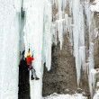 Ice climber struggles up a frozen waterfall. - Stock Photo
