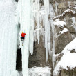 Stock Photo: Ice climber struggles up frozen waterfall.
