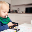 Adorable baby boy using wax crayons — Stock Photo