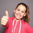 Cheerful young girl giving a thumbs up — Stock Photo