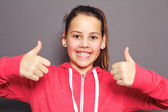 Enthusiastic young girl giving thumbs up — Stock Photo
