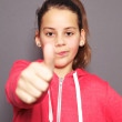 Dubious young girl giving a thumbs up - Stock Photo
