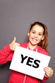 Enthusiastic happy little girl with YES sign — Stock Photo