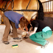 Two woman working on a horseshoe — Stok fotoğraf